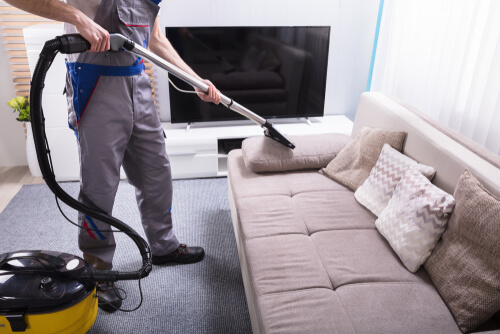 Man Cleaning Sofa In The Living Room Using Vacuum Cleaner At Home
