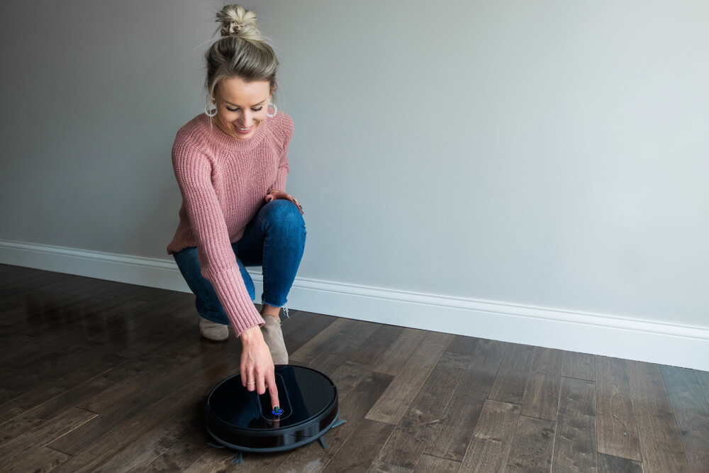 A Young woman starting her robotic vacuum